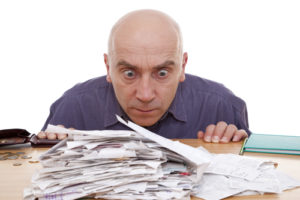 heap of receipts and terrified man